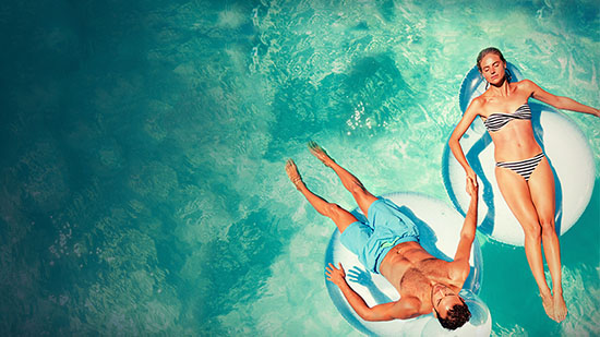 Fundraising image - Couple floating in pool toys in the ocean