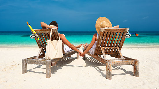 Fundraing image - A couple relaxing on a sandy beach