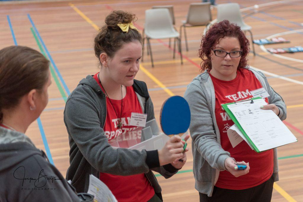 Volunteers teaching the rules of boccia to other volunteers