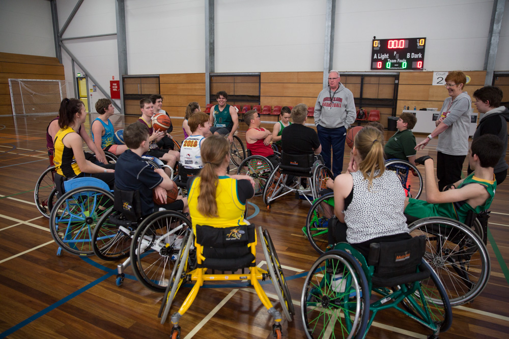 Wheelchair basketballers listening to coach at 2018 junior development camp