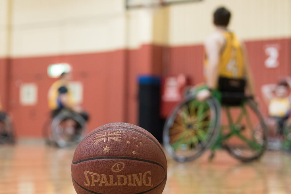Basketball with wheelchair basketball player in the background