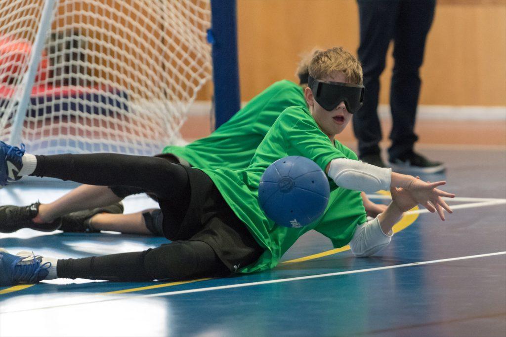 Junior male goalballer blocking the goalball
