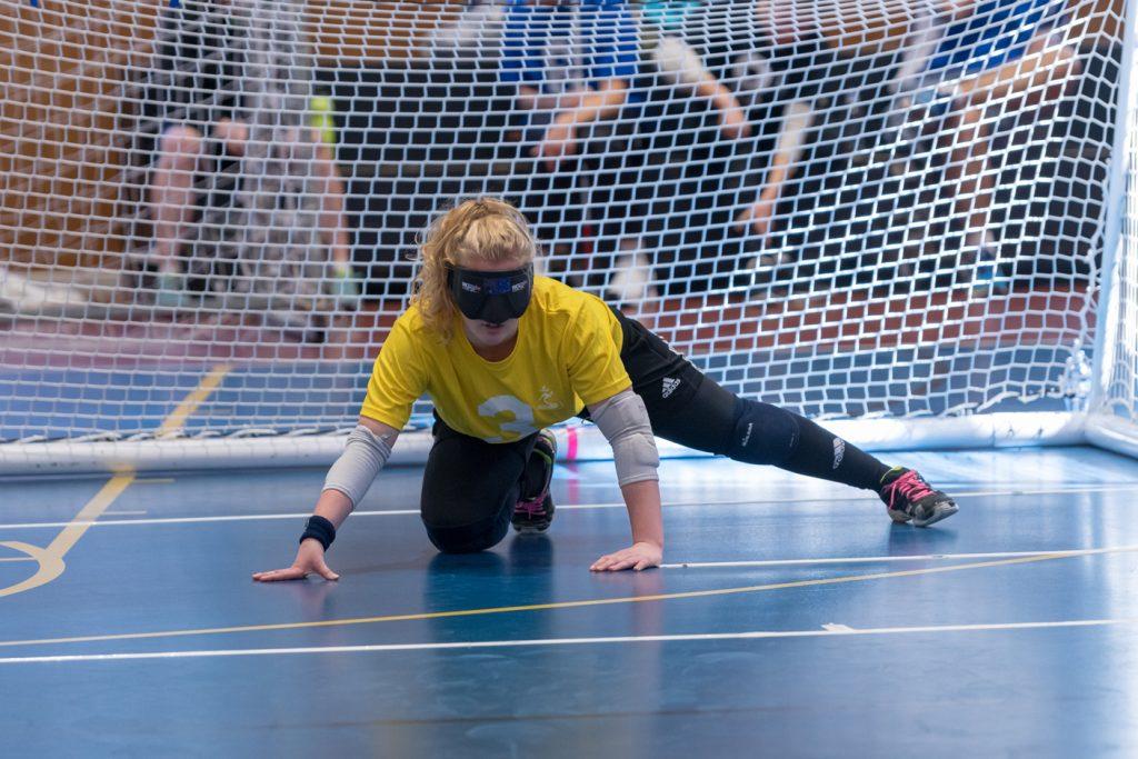 Female goalballer kneeling down waiting for the ball