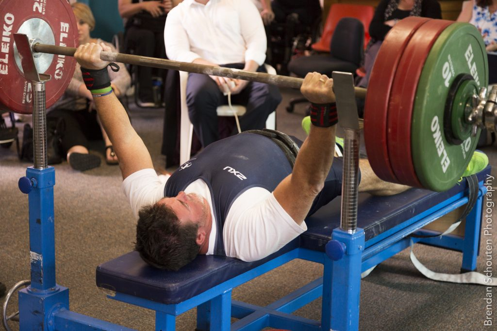 Para powerlifter lying on powerlifting bench