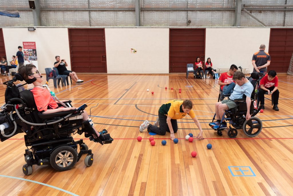 Boccia players watching their referee measure their the distance between the jak and balls