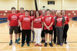 Group shot of volunteers wearing red sporting wheelies shirts